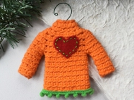 Sweater ornament in orange with a red heart and green pompoms